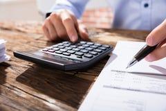 Person Calculating Finance Using Calculator Fotografía de archivo libre de regalías