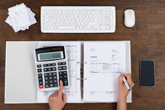 Person Calculating Invoice With Calculator Stock Photo
