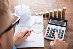 Person Calculating Invoice On Desk. High Angle View Of A Auditor Hand Calculating Invoice Using Calculator On Desk. Tax Scrutiny And Fraud Investigation Concept stock photos