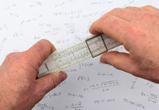 Person calculating on a slide rule Stock Images