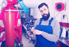 Person is calculating sum for repairing motorcycle. In workshop Stock Photos