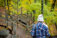 Person with camera walking in woods in fall stock photo