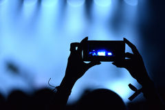 Person capturing video on a mobile phone at a music festival Stock Photo