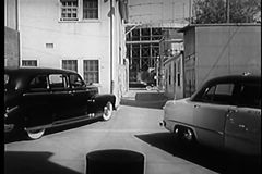 Person in car driving through alley to tail other car, 1950s stock video