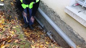 A person carries out plumbing work to replace a water pipe. Outside the house stock footage