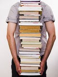 Person carrying books. A studio view of a person carrying a tall stack of books Stock Photos