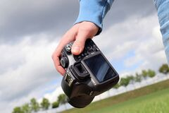 Person carrying digital camera outdoors Stock Photography