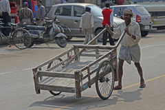 Person Carrying an Empty Barrow Stock Photo