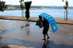 Person carrying inflatable beach mattresses and other beach stuff as protection during summer shower on paved road next to beach royalty free stock photo