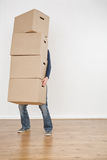 Person Carrying Moving Boxes. A person carrying a heavy stack of moving boxes into an empty new house Stock Images