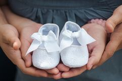 Person Carrying Pair of Baby's White Flats Stock Photo