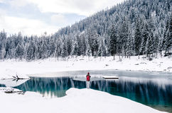 Person Carrying Red Backpack Standing on Snow Covered Road Beside Body of Water during Daytime Royalty Free Stock Photos