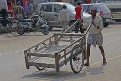 Person Carrying um carrinho de mão vazio Foto de Stock