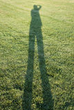 Person casting shadow on grass Royalty Free Stock Images