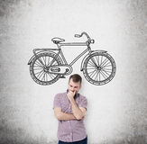A person in casual clothes is thinking about affordable or environmental friendly ways of travelling. A sketch of bicycle is drawn Stock Photography