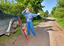 The person changes a wheel at the car by means of a red rack jack Royalty Free Stock Photography