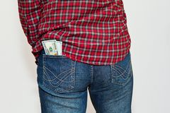 Person in checkered shirt with money in back pocket Stock Photo