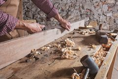 Person with chisel scraping wood off long beam. On top of table next to mallet and curled wooden scraps royalty free stock photography