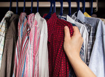 Person chooses shirt in the closet. Of the multi-colored shirts Royalty Free Stock Images