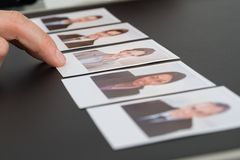 Person choosing photograph of a candidate. Close-up Of A Person's Hand Choosing Photograph Of A Candidate Royalty Free Stock Photography