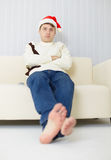 Person in a Christmas cap sits on sofa Royalty Free Stock Photo