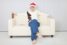 Person in a Christmas cap sits on sofa with beer Stock Photo