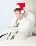 Person in Christmas hat gives us money Stock Photo