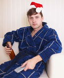 Person in christmas hat sits on sofa with beer Royalty Free Stock Images