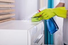 Person Cleaning Furniture With Spray-Fles stock afbeeldingen