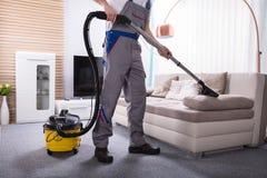 Person Cleaning Sofa With Vacuum-Reinigingsmachine stock foto