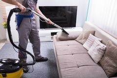 Person Cleaning Sofa With Vacuum-Reinigingsmachine royalty-vrije stock foto's