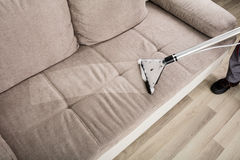 Person Cleaning Sofa With Vacuum rengöringsmedel royaltyfri foto