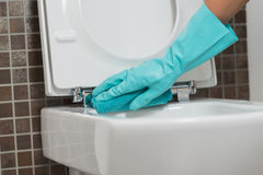 Person cleaning the toilet seat in rubber gloves. Hand of a person cleaning the toilet seat in rubber gloves with a sponge disinfecting the underside for germs Stock Images