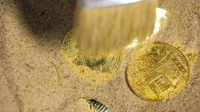Person cleans sand from coins created as currency. Slow motion macro person uses brush to clean sand from coins created as bitcoin currency which issuance stock footage