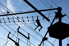Person climbing on high ropes. One Person climbing on high ropes Royalty Free Stock Photography