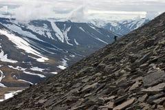A Person Climbing Steep Mountainside Stock Photos