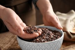 Person with cocoa nibs in hand over bowl. On table royalty free stock photos