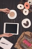 Person with coffee, digital tablet and donuts Royalty Free Stock Photos