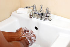 Person of colour washing hands in sink Royalty Free Stock Image
