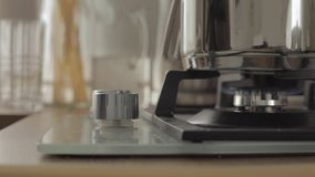 Person comes to gas stove and turns it on, then turns it off on kitchen stock footage
