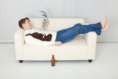 Person comfortably lie on sofa with journal Royalty Free Stock Image