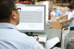 Person At Computer Terminal In Distribution Warehouse. Working royalty free stock photography