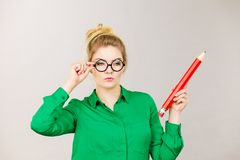 Woman confused thinking, big pencil in hand stock photo