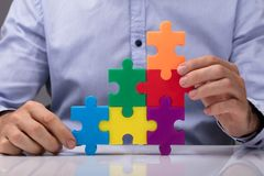 Person Connecting Multicolored Jigsaw Puzzle photo stock