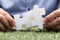 Person Connecting Two White Jigsaw-Raadsel royalty-vrije stock afbeelding