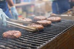 Person Cooking Burgers en parrilla de la barbacoa que fuma Foto de archivo libre de regalías