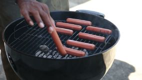 A person is cooking sausage on grill stock footage