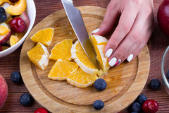 The person cooks fruit salad. Stock Image
