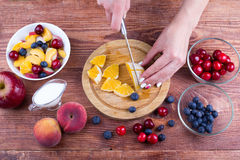 The person cooks fruit salad. Stock Photos