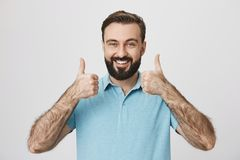 Person with cute beard and moustache thumbs up to show his positive answer standing near white wall. Mature male wearing. Person with cool beard and moustache Stock Photography